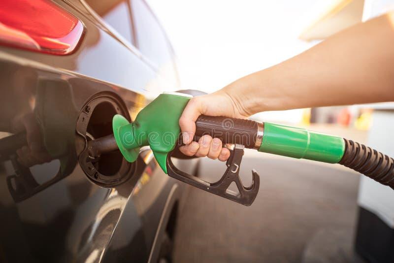 Primo piano del combustibile di pompaggio della benzina dell'uomo in automobile alla stazione di servizio immagini stock