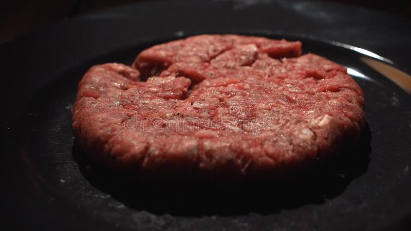 Primo piano del cuoco del cuoco unico che prende una cotoletta dalla pentola nera per la cottura degli hamburger Metraggio di ris immagini stock