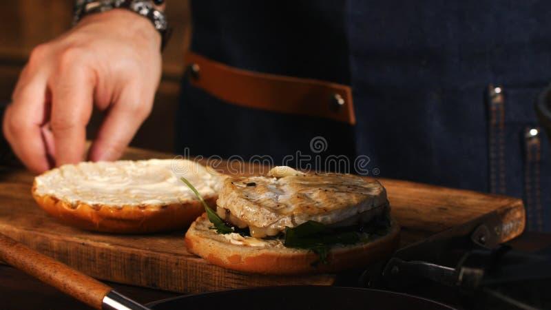 Primo piano del cuoco unico maschio in grembiule blu che aggiunge i verdi su un panino di hamburger fritto Metraggio di riserva P fotografie stock