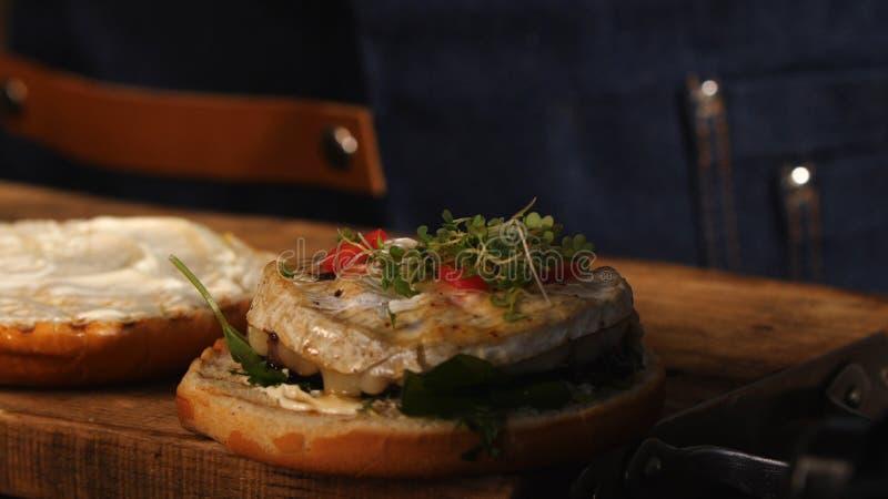 Primo piano del cuoco unico maschio in grembiule blu che aggiunge i verdi su un panino di hamburger fritto Metraggio di riserva P immagini stock