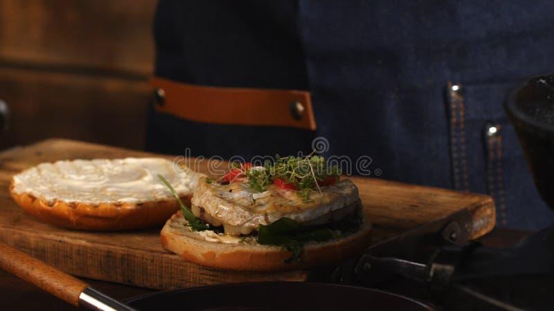 Primo piano del cuoco unico maschio in grembiule blu che aggiunge i verdi su un panino di hamburger fritto Metraggio di riserva P immagine stock libera da diritti