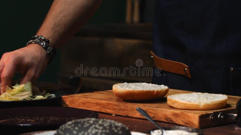 Primo piano del cuoco unico maschio in grembiule blu che rimuove i verdi in eccesso da un panino di hamburger Metraggio di riserv immagine stock