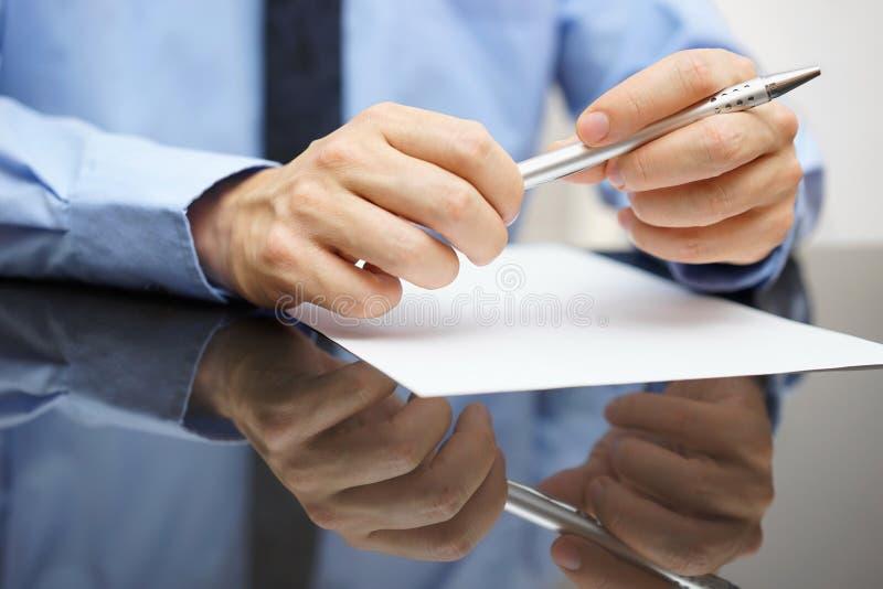 Primo piano del documento o del contratto della lettura dell'uomo di affari fotografia stock libera da diritti