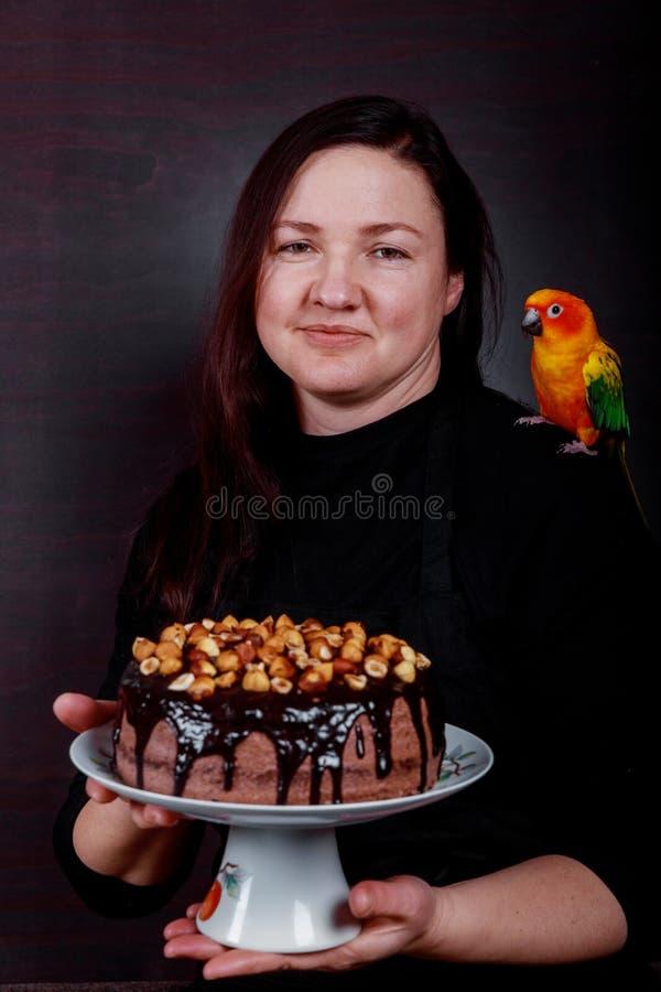 Primo piano del dolce femminile della tenuta del cuoco unico che mostra un dolce saporito contro il fondo scuro fotografia stock