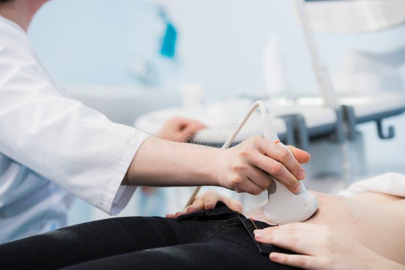 Primo piano del dottore Moving Ultrasound Probe sullo stomaco del ` s della donna incinta in ospedale immagini stock