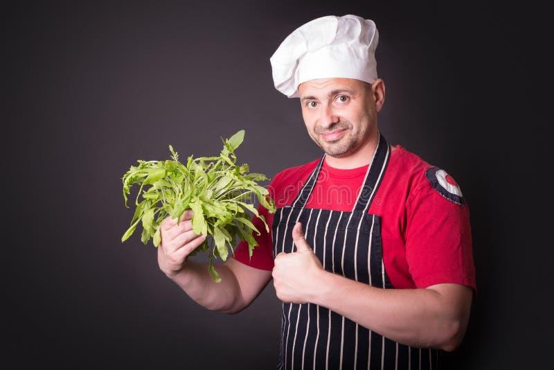 Primo piano del fascio felice della rucola della tenuta del cuoco unico immagine stock libera da diritti
