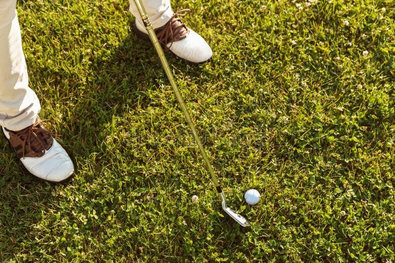 Primo piano del giocatore di golf maschio che colloca sul tee fuori fotografie stock
