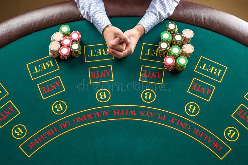 Primo piano del giocatore di poker con i chip alla tavola verde del casinò immagine stock