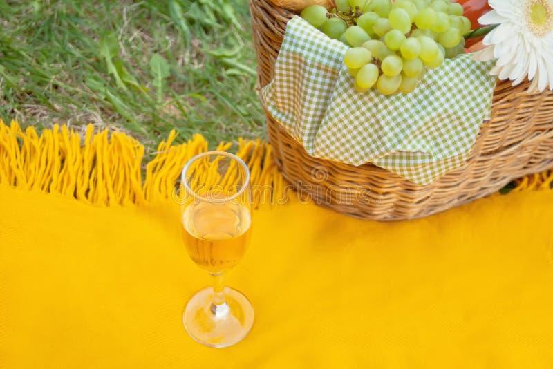 Primo piano del glasse del vino sulla copertura gialla, canestro di picnic con alimento e fiore sull'erba verde fotografie stock libere da diritti