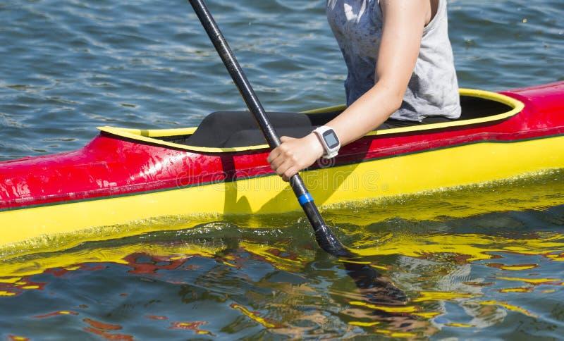 Primo piano del kayaker femminile che rema attraverso le rapide dell'acqua fotografie stock libere da diritti