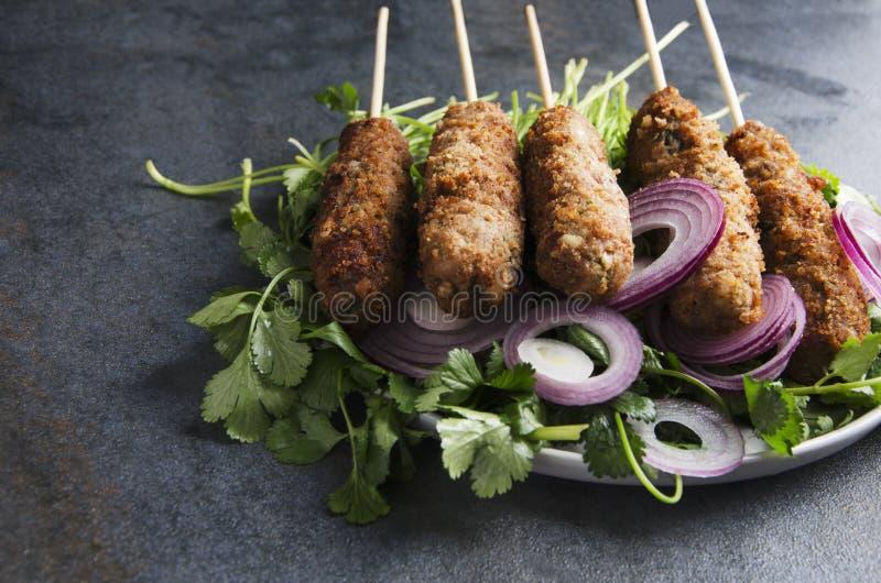 Primo piano del kebab cucinato saporito di lyulya sul mucchio di coriandolo e dello scalogno affettato sulla tavola scura, sullo  immagini stock