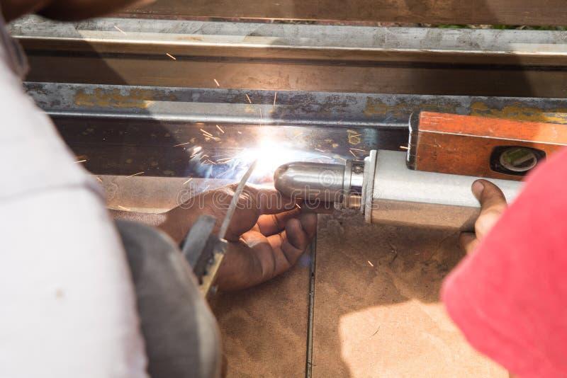 Primo piano del lavoratore che salda il braccio automatico del portone sul portone del metallo immagini stock