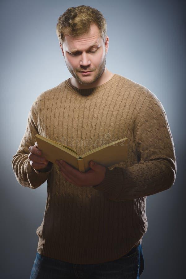 Primo piano del libro di lettura confuso dell'uomo contro fondo grigio immagine stock