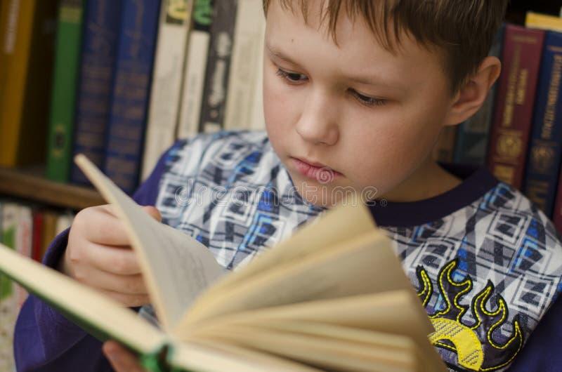 Primo piano del libro di lettura sveglio del ragazzo in biblioteca fotografie stock libere da diritti
