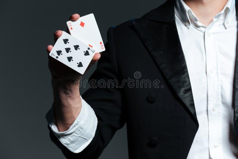 Primo piano del mago dell'uomo che tiene due carte da gioco immagine stock libera da diritti