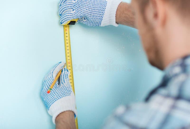 Primo piano del maschio in guanti che misurano parete con nastro adesivo fotografia stock