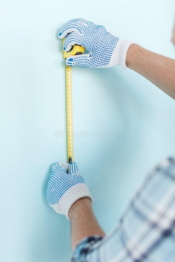 Primo piano del maschio in guanti che misurano parete con nastro adesivo immagini stock libere da diritti