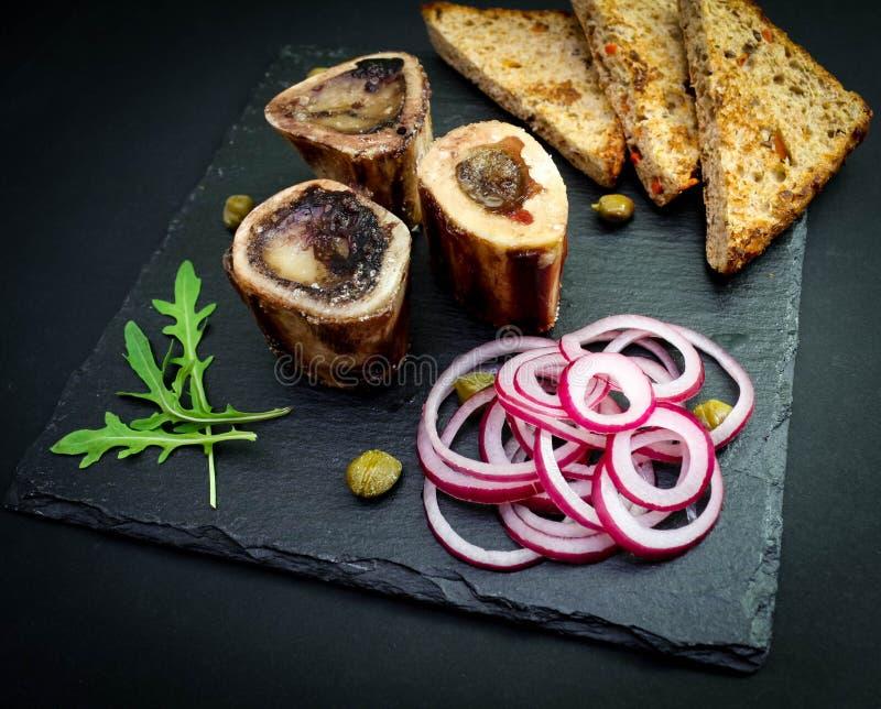Primo piano del midollo osseo inglese rustico con pane tostato, i capperi e le cipolle immagini stock libere da diritti
