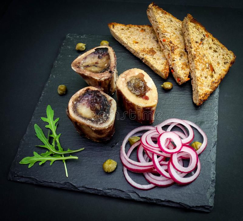 Primo piano del midollo osseo inglese rustico con pane tostato, i capperi e le cipolle fotografie stock