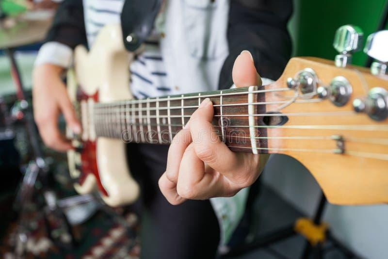 Primo piano del Midsection della donna che gioca chitarra immagini stock libere da diritti