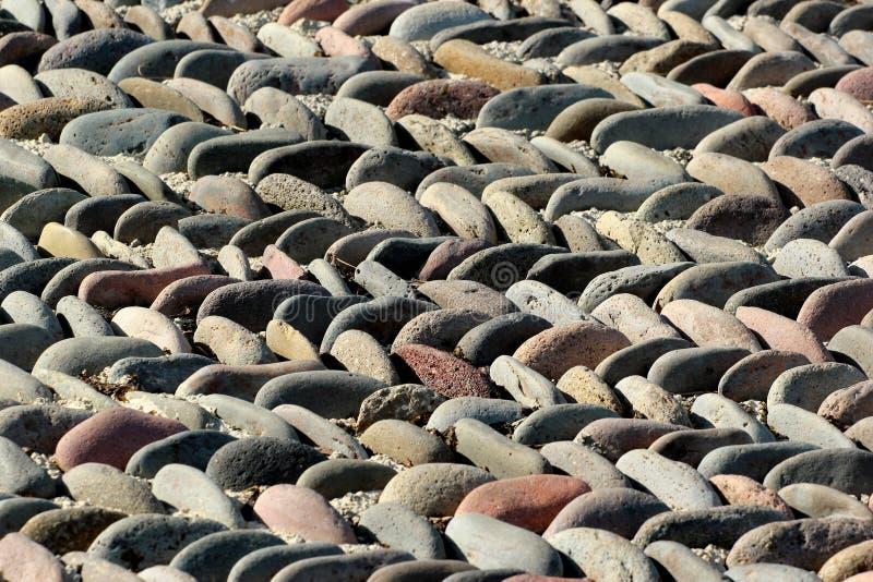 Primo piano del modello della pavimentazione del ciottolo Fondo di pietra del mosaico fuoco fotografie stock