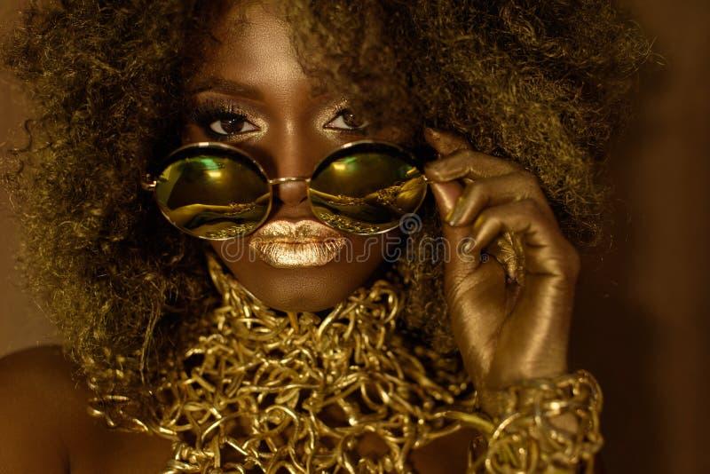 Primo piano del modello femminile afroamericano dorato magico in occhiali da sole massicci con trucco luminoso di scintillio, luc immagini stock