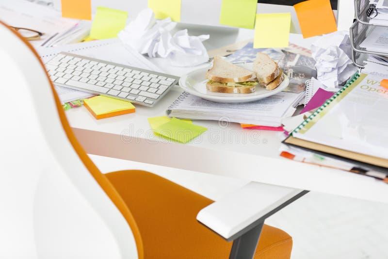 Primo piano del panino e dei documenti allo scrittorio del computer in ufficio fotografia stock libera da diritti