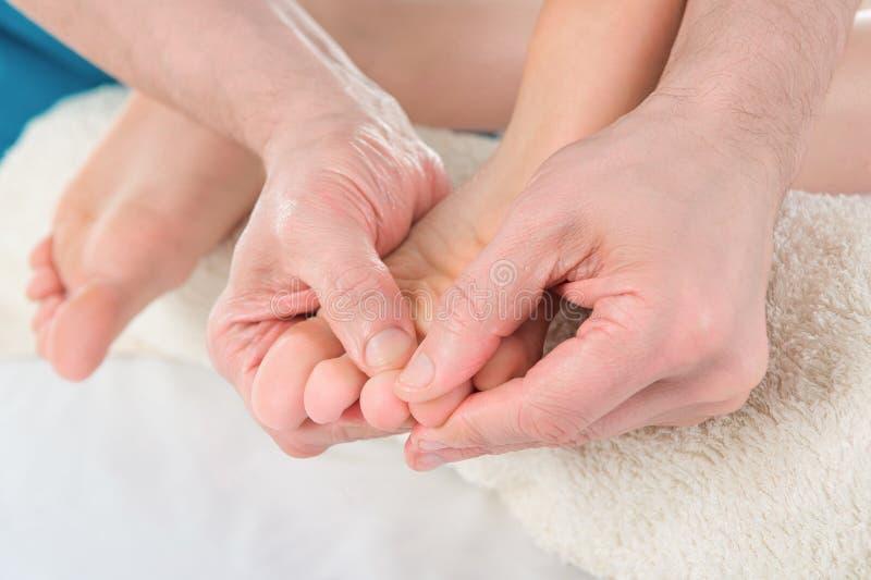 Primo piano del piede della donna che riceve trattamento di massaggio da un therap fotografia stock libera da diritti