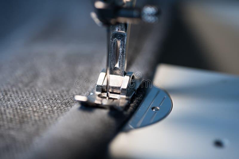 Primo piano del piede e dell'ago della macchina per cucire fotografia stock