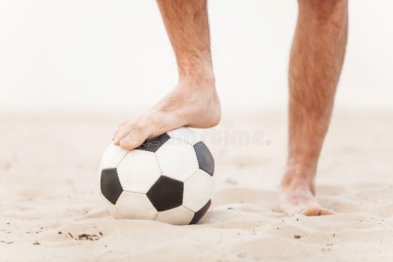 Primo piano del piede maschio che gioca a calcio sulla sabbia immagine stock libera da diritti