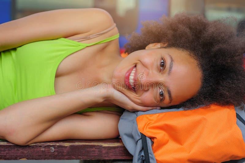Primo piano del pisolino turistico di viaggiatore con zaino e sacco a pelo femminile su un banco immagini stock