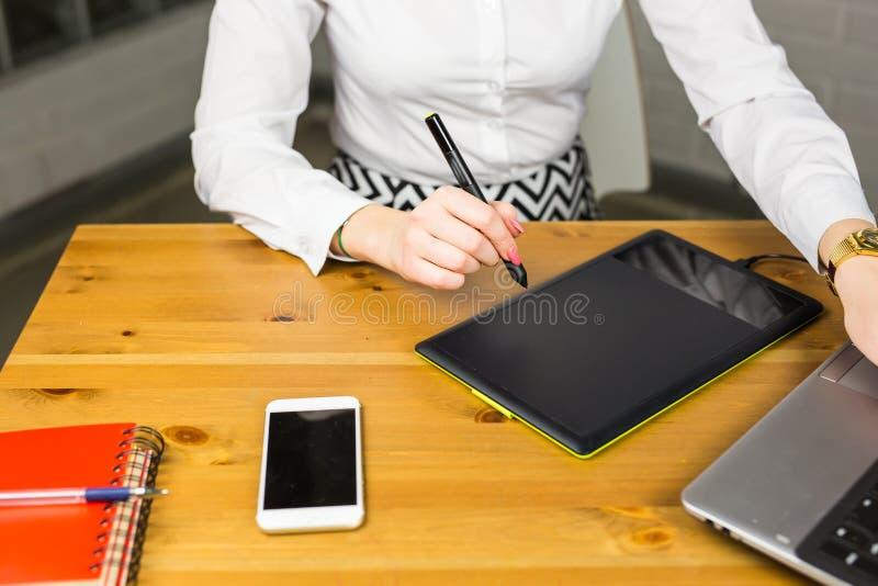 Primo piano del progettista femminile in ufficio che lavora con la tavola ed il computer portatile del grafico digitale Retoucher fotografie stock libere da diritti