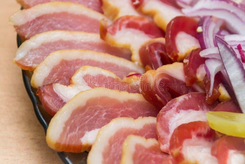 Primo piano del prosciutto, del bacon, della lattuga, del cetriolo e della cipolla su carta, su un vassoio fotografie stock libere da diritti