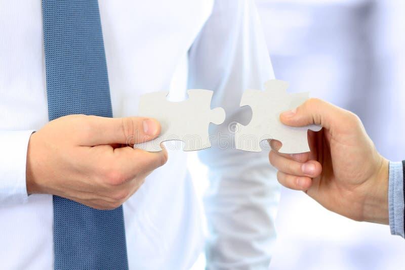 Primo piano del puzzle di collegamento della mano degli uomini d'affari immagini stock