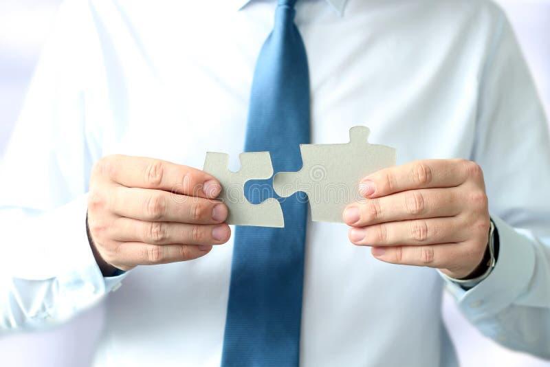 Primo piano del puzzle di Hands Connecting Jigsaw dell'uomo d'affari fotografie stock libere da diritti