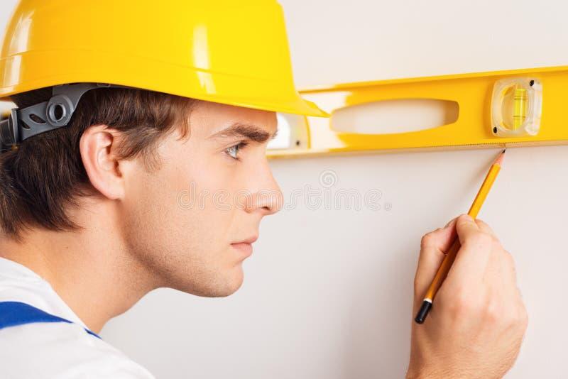 Primo piano del riparatore che misura con il livello del costruttore immagini stock