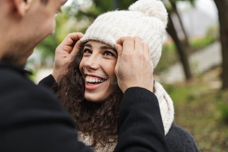 Primo piano del ritratto dell'uomo adorabile della gente e della donna 20s che abbracciano e che sorridono, mentre camminando att immagine stock libera da diritti