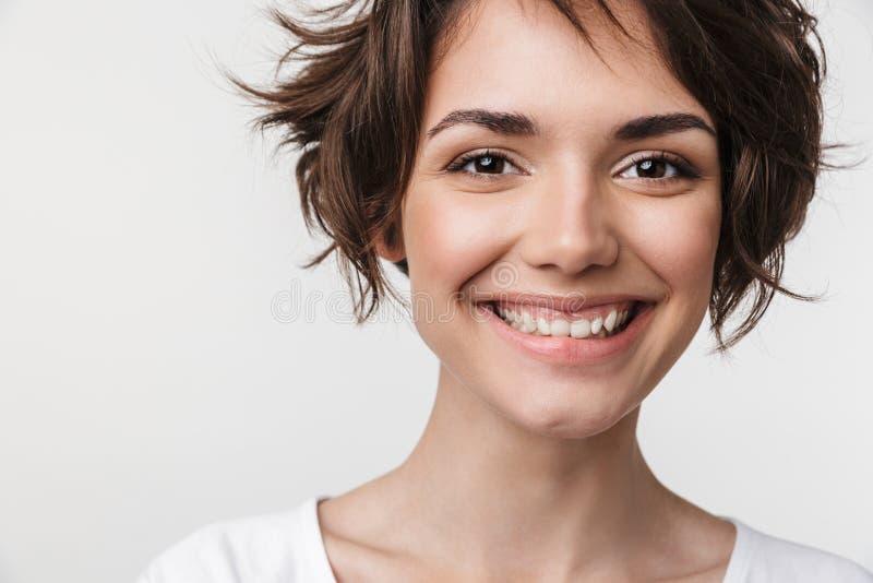 Primo piano del ritratto della donna graziosa con brevi capelli marroni in maglietta di base che sorride alla macchina fotografic fotografia stock libera da diritti
