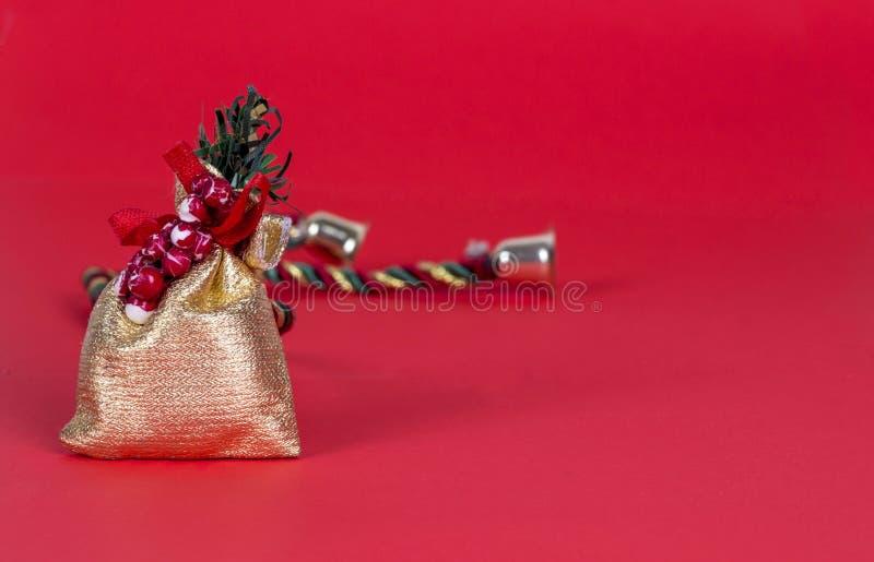 Primo piano del sacco dorato o di poco sacchetto per il regalo isolato su fondo rosso fotografia stock