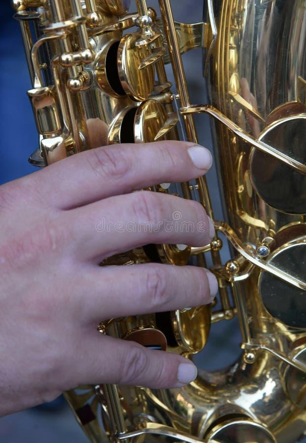 Primo piano del sassofono dello strumento musicale Mani del sassofonista che giocano sassofono immagini stock