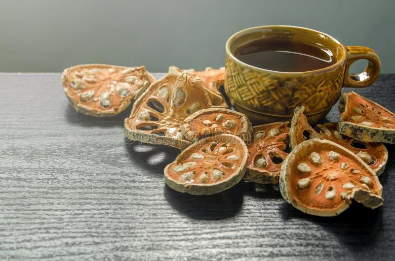 Primo piano del tè di cotogno del bengala e del succo asciutti e di vetro di cotogno del bengala sul pavimento di legno fotografie stock
