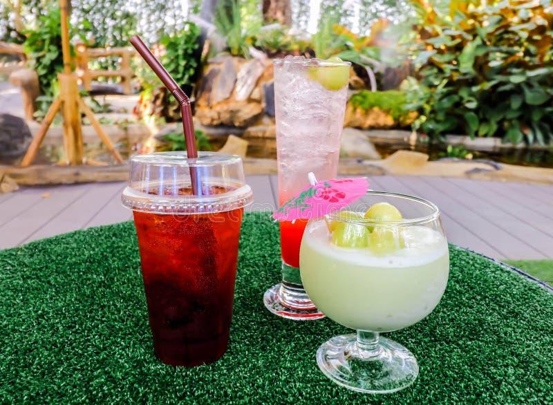 Primo piano del tè del limone, della soda della fragola e del succo ghiacciati del melone sulla tavola fotografie stock libere da diritti