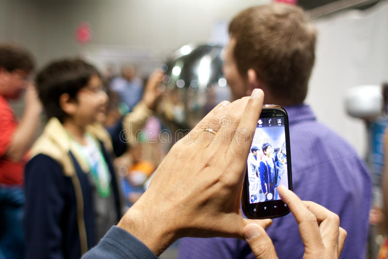 Primo piano del telefono della macchina fotografica che prende immagine all'Expo di scienza fotografia stock libera da diritti