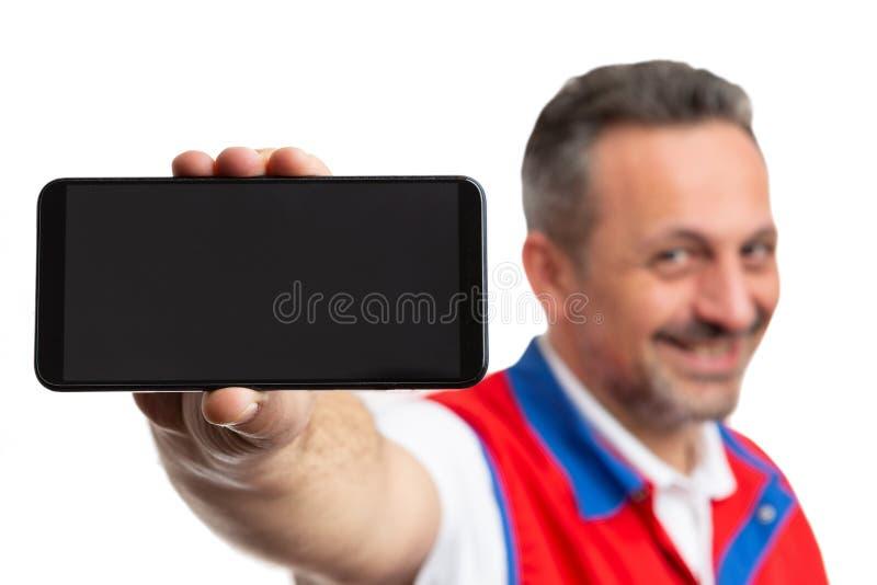 Primo piano del telefono tenuto dall'impiegato del supermercato immagini stock libere da diritti