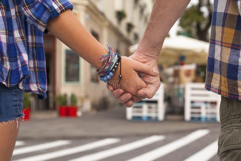 Primo piano del tenersi per mano di giovane coppia in una città di estate romantico fotografia stock