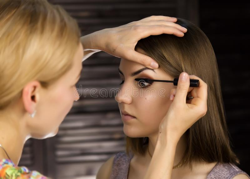 Primo piano del truccatore professionista che applica eye-liner sulla palpebra Lo stilista sta facendo compensa la femmina dall'e fotografie stock libere da diritti