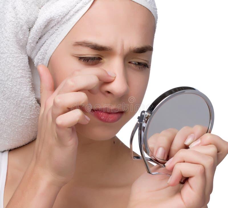 Primo piano dell'adolescente che trova un'acne sul suo naso immagine stock libera da diritti