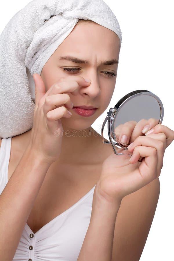 Primo piano dell'adolescente che trova un'acne sul suo naso fotografia stock