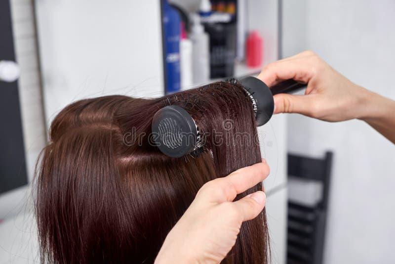 Primo piano dell'apprettatrice dei capelli che pettina i capelli del ` s del cliente in salone fotografia stock libera da diritti
