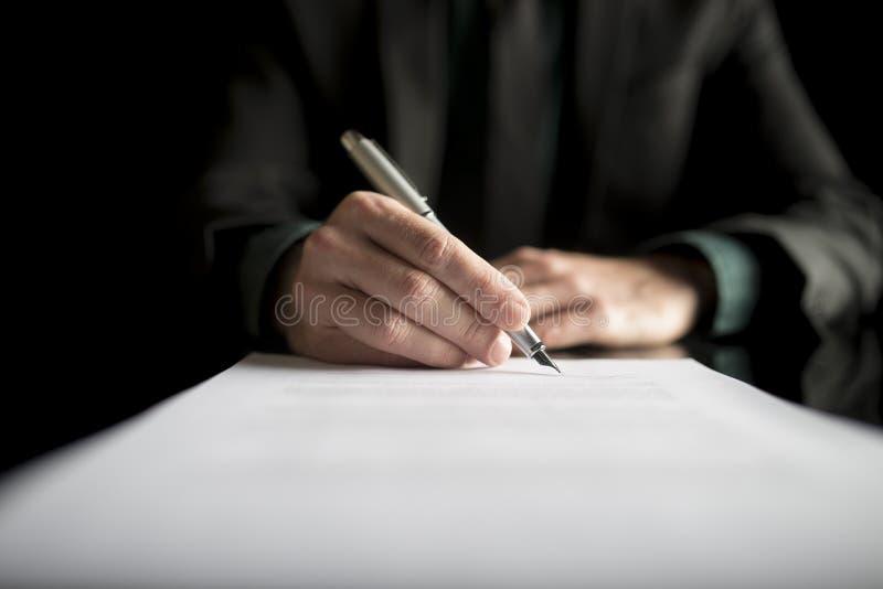 Primo piano dell'avvocato o del dirigente che firma un contratto immagine stock libera da diritti